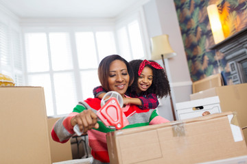 Affectionate mother and daughter packing, moving house