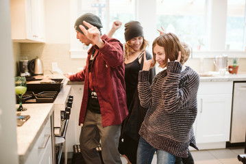 Carefree family dancing and cooking in kitchen