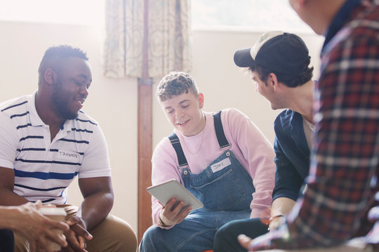 Men with digital tablet talking in group therapy