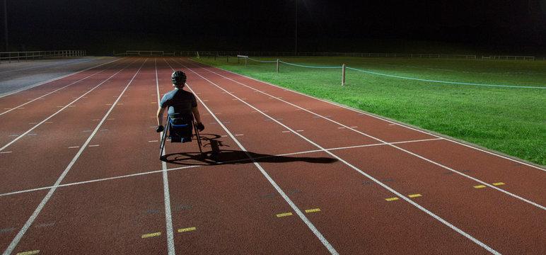 Paraplegic athlete training for wheelchair race on sports track at night