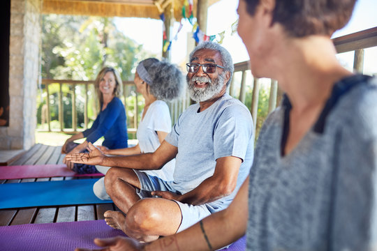 Senior man talking with woman in hut during yoga retreat