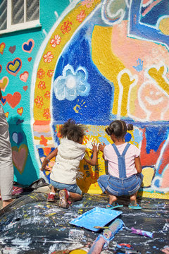 Girls painting vibrant mural on sunny wall