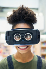 Portrait silly, cross-eyed junior high girl student wearing virtual reality simulator