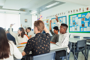 High school students with hands raised asking questions during lesson in classroom