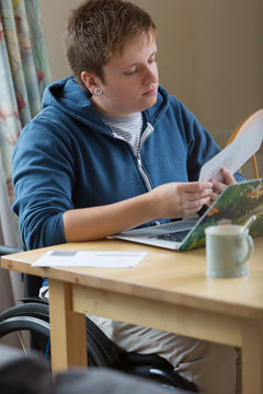 Young woman in wheelchair paying bills at laptop