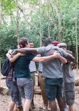 Mens group hugging in huddle, hiking in woods