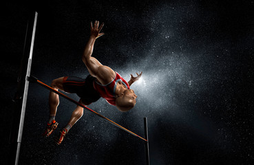 Male track and field athlete high jumping