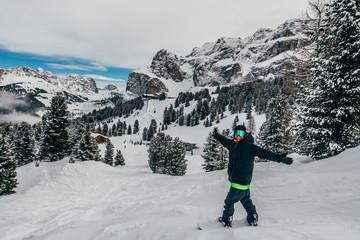 Portrait exuberant snowboarder on snowy ski slope, Dolomites, Italy