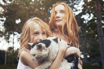 Sisters holding cat
