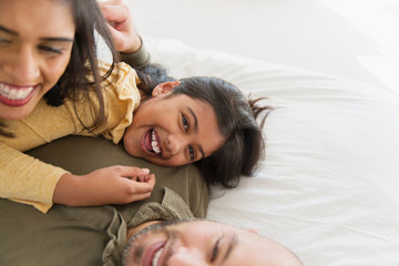 Portrait happy parents and daughter cuddling on bed
