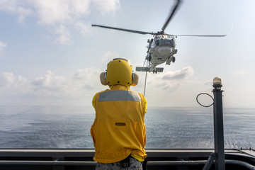 Printed roller blinds Helicopter Helicopter deck officer give hand signal to Sikorsky S-70 Sea Hawk helicopter hovering above helicopter deck of Navy ship to perform hot refueling while flying at sea.