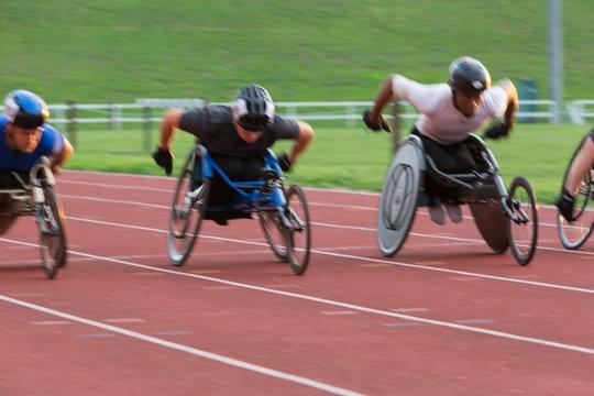 Determined paraplegic athlete speeding along sports track in wheelchair race