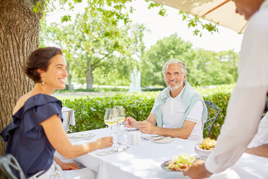 Waiter serving food to mature couple dining at patio table