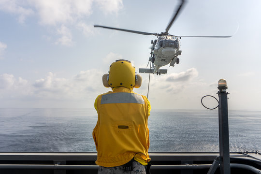 Helicopter deck officer give hand signal to Sikorsky S-70 Sea Hawk helicopter hovering above helicopter deck of Navy ship to perform hot refueling while flying at sea.