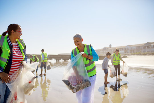 Volunteers cleaning up litter on sunny, wet sand beach