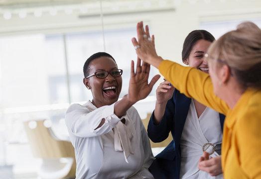 Businesswomen high-fiving in office