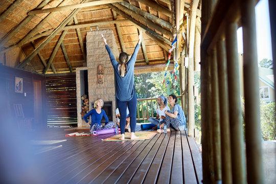 Woman leading yoga retreat in hut