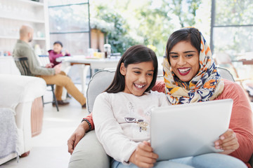 Happy mother in hijab and daughter using digital tablet