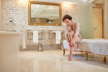 Woman putting on high heel sandals in luxury hotel bathroom