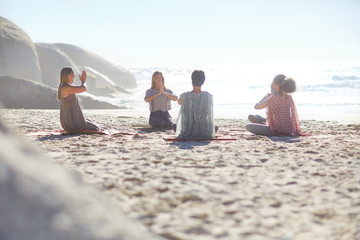 Group meditating in circle on sunny beach during yoga retreat