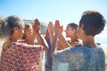 Group standing in circle hands clasped on sunny beach during yoga retreat