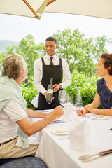 Wine steward showing wine bottle to couple dining at patio table