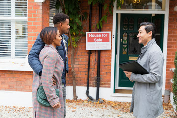Real estate agent talking with couple outside house for sale