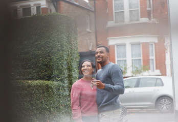 Happy couple with house keys outside new house
