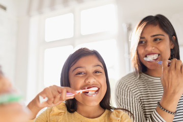 Portrait happy mother and daughter brushing teeth in bathroom