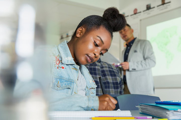 Focused high school girl student studying in classroom