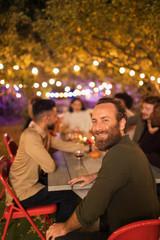 Portrait happy man enjoying dinner garden party