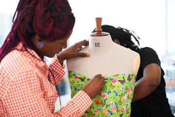 Female fashion designers pinning butterfly fabric on dressmakers model Wall mural
