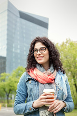 Smiling woman drinking coffee in urban park