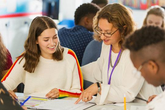Female high school teacher helping girl student with homework in classroom