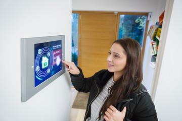 Woman leaving house, setting smart home alarm