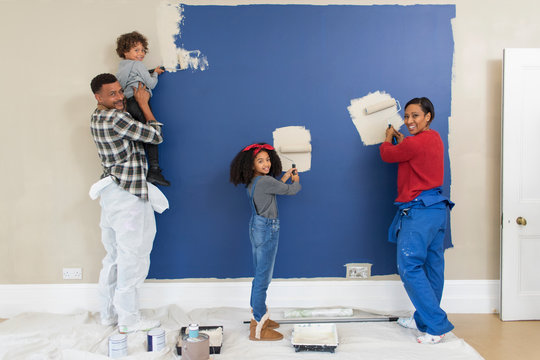 Portrait happy family painting wall