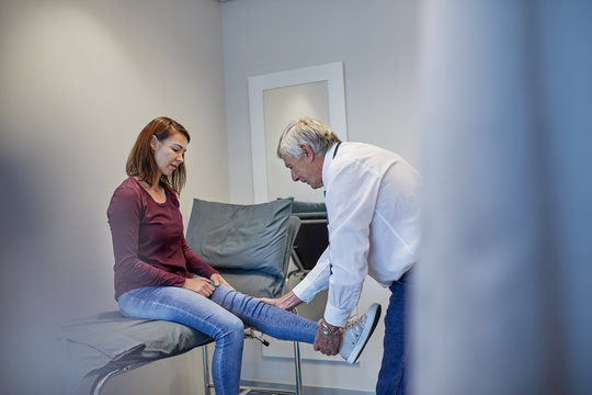 Male doctor examining womans leg in clinic examination room