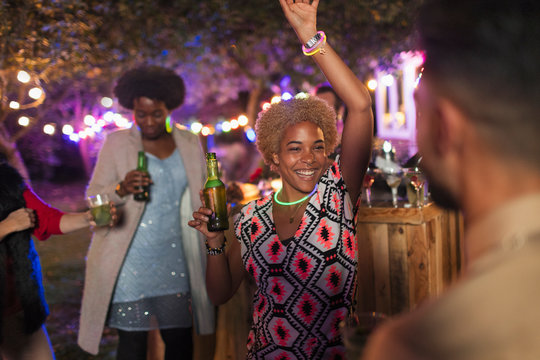 Carefree woman dancing and drinking at garden party