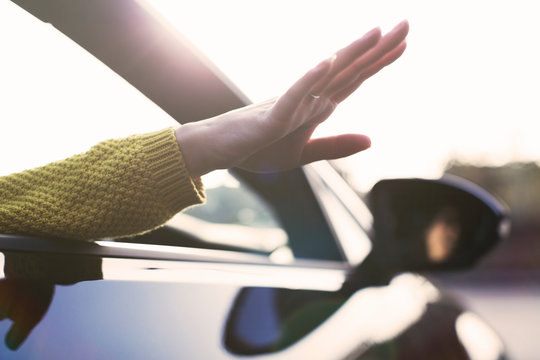 Carefree woman reaching hand out car window