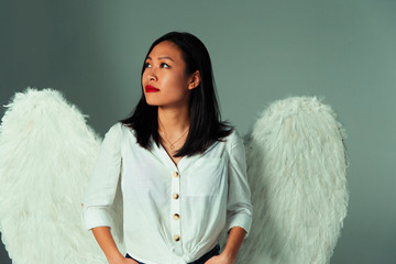 Serene, curious young woman wearing angel wings Fotoväggar