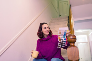 Smiling woman redecorating, looking at paint swatch on stairs