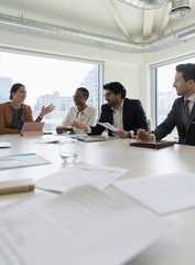 Business people discussing paperwork in conference room meeting