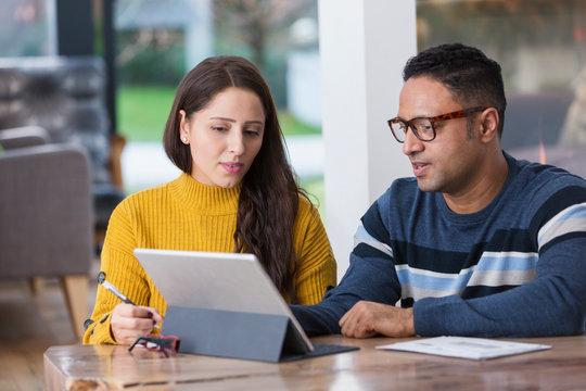 Couple paying bills at digital tablet