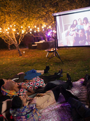 Friends relaxing, watching movie on projection screen in backyard