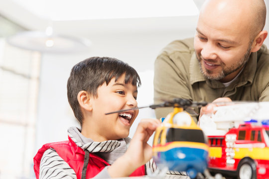 Father and son playing with helicopter and fire engine toys