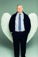 Portrait smiling businessman wearing angel wings