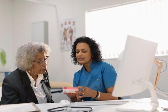 Female doctor prescribing medication to senior patient in doctors office