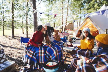 Affectionate lesbian couple with kids kissing at sunny campsite in woods