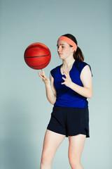 Teenage girl basketball player spinning basketball on finger