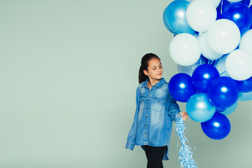 Smiling girl with blue and white balloon bunch